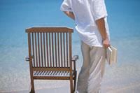 砂浜に立つ男性と椅子