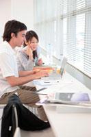 ノートパソコンを操作する外国人男性と女性