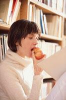 本棚の前でリンゴをかじる女性