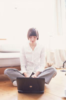 床に座ってノートパソコンを打つ女性