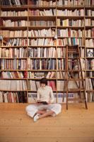 本棚の前で本を読む外国人女性