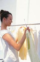 ハンガーにかかった服を選ぶ女性