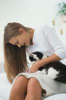リビングのソファで猫をなでる女性