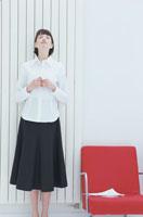 赤い椅子の脇に立った女性