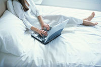 ベットの上でノートパソコンをする女性