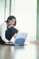 床に座ってノートパソコンをする女性