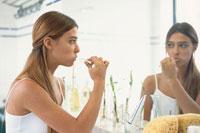 バスルームで歯を磨く女性
