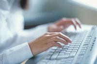 パソコンのキーボードを打つ女性の手元