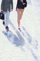 石畳の道を歩くビジネススタイルの男女