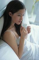 ベットに座りコーヒ−カップを持った女性