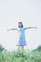 草原で両手を広げたワンピースの少女