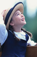 帽子に手をあて上を見上げる少女