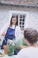 庭のテーブルで鉢植えをするカップル