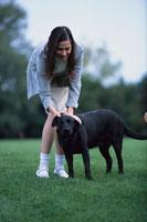 庭で黒いラブラドール犬を撫でる女性