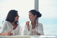 海辺のカフェテラスで話をする女性2人