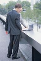 道でノートパソコンを開くスーツの男女 21007004424| 写真素材・ストックフォト・画像・イラスト素材|アマナイメージズ