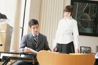 デスクに座る男性と脇に立つ女性 21007004448| 写真素材・ストックフォト・画像・イラスト素材|アマナイメージズ