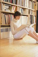 本棚の前に座り本を読む女性