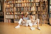 本棚の前に座り本を読む女性2人