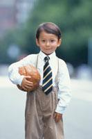 革のボールを持って立つ少年