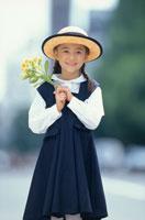 帽子をかぶって花を持った少女