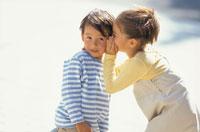 少年の耳元に手を当て話す少女