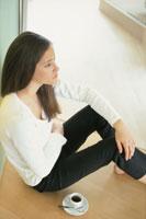 床に座り壁に寄りかかった女性 21007004590| 写真素材・ストックフォト・画像・イラスト素材|アマナイメージズ