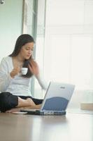 床に座りノートパソコンをする女性