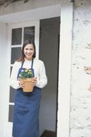 鉢植えを持って戸口に立つ女性