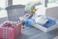 テラスのテーブルの上のティーポットと贈物