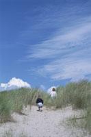 砂の上を歩く子供2人後姿