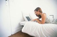 ベッドでノートPCをさわる女性