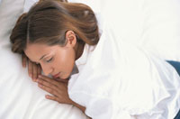 ベッドでうつぶせになる女性