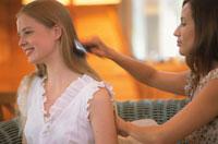 ソファで髪を梳かす女性2人
