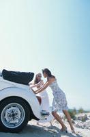 砂浜で白いオープンカーを押す女性2人 21007005049| 写真素材・ストックフォト・画像・イラスト素材|アマナイメージズ