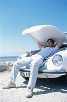 車のボンネットを開けて休む男性