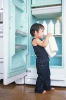 冷蔵庫から牛乳を出す男の子