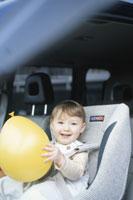 黄色い風船を持ってチャイルドシートに座る幼児