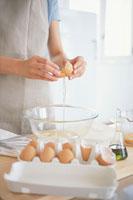 ボールに卵を割る女性の手元