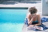 プールサイドで雑誌を読む女性