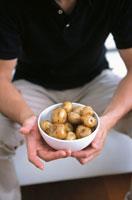 じゃがいも料理を手にする男性 21007005135| 写真素材・ストックフォト・画像・イラスト素材|アマナイメージズ