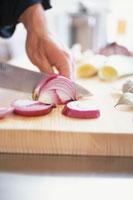 まな板で玉葱を切る男性の手元
