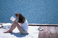 桟橋でくつろいで読書する女性