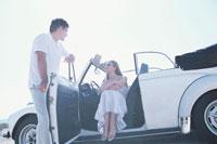 白いオープンカーとカップル