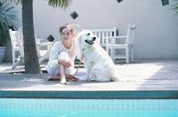 プールサイドに座る女性と犬