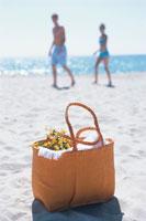 ビーチに置かれたバッグとカップル