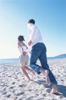 砂浜を走る男女のカップル