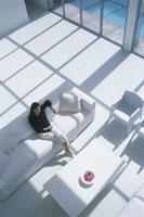 白いリビングルームのソファに座る外国人女性