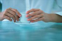 女性が手を添えた白いコーヒーカップ