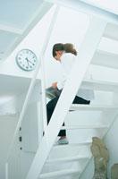 白い階段に座り読書する女性